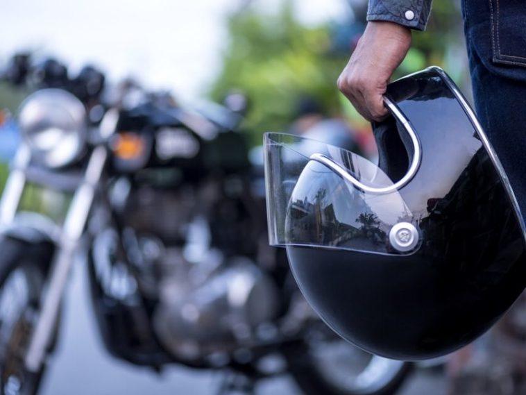 motorcyclist holding a black helmet
